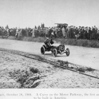 Car No. 16 taking a curve passed the crowd along the Motor Parkway during the Vanderbilt Race
